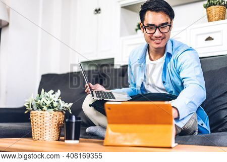 Young Smiling Asian Man Using Laptop Computer Working And Video Conference Online Meeting With Colle