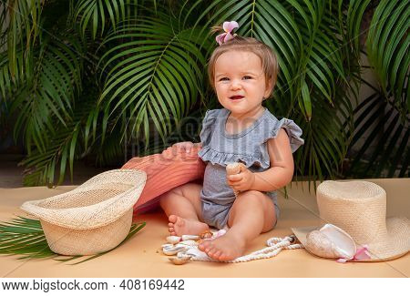 Child With Seashells On A Background Of Palm Trees. The Baby Sits Under Palm Trees And Plays With Se