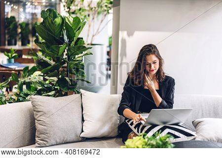 Portrait Of Smiling Happy Beautiful Woman Relax Using Technology Of Smartphone And Looking At Laptop