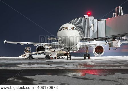Front View Of The Passenger Aircraft Stands At The Jetway On Night Airport Apron. The Baggage Compar