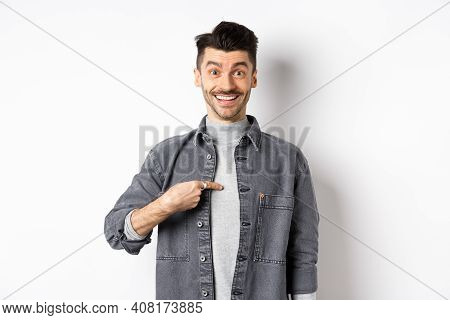 Is It Me. Surprised Happy Guy Pointing At Himself, Smiling Cheerful, Being Chosen, Standing On White