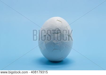 A White Boiled Egg With A Cracked Shell Close-up On A Blue Background. Free Space. Cracked Eggshell