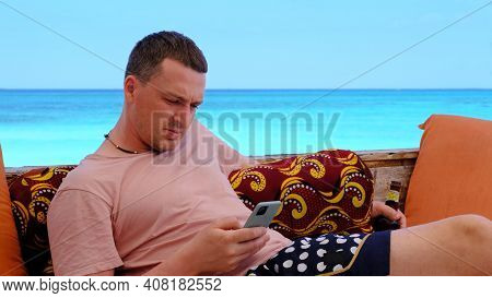 Young Man With Beer Bottle Surfs Internet With Phone At Comfortable Lounge Zone On Picturesque Ocean