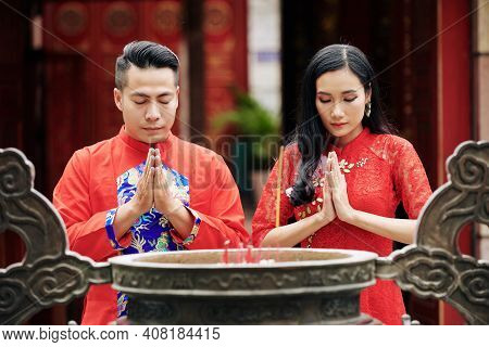 Young Couple Standing With Eyes Closed And Holding Hands In Pray Gesture When Standing At Ancient Br