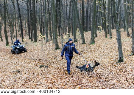 A Rescuer With A Dog On A Leash Searches In The Woods, A Rescuer On An Atv Also Searches. Search For