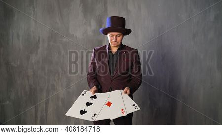 The Magician Shows Trick With Playing Cards. Closeup Of Man Magician With Two Playing Cards In His H