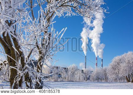 Thermal power station with smoking pipes at sunny day in winter