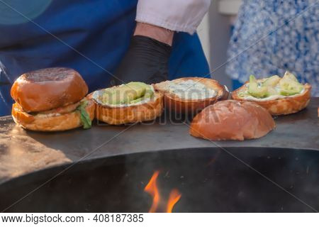 Process Of Preparing Burgers With Seafood And Avocado On Brazier With Hot Flame At Summer Local Food