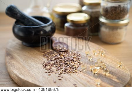 Horizontal Photo With Wooden Spoon Full Of Flax Seeds Next To Small Glass Bottle With Flax Oil And B