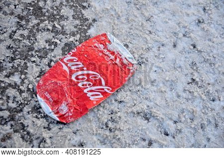 Moscow, Russian Federation - February 14, 2021: Coca-cola Can Flattened Under The Wheels Of Cars On
