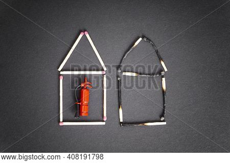 Two Houses Made Of Burnt And Unburnt Matches With A Miniature Fire Extinguisher Inside The Undamaged