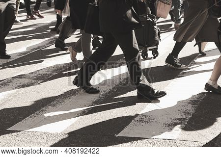 Unrecognizable And Blurry People Crossing The Road At A Pedestrian Crossing. Close-up At Legs.