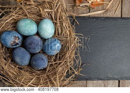 Easter Background With Easter Eggs In A Nest On A Wooden Table. Top View With Copy Space.