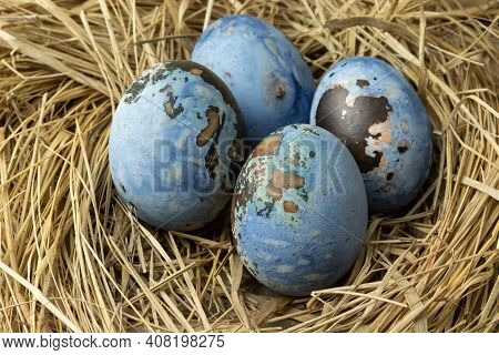 Colorful Easter Eggs In A Nest On A Wooden Table.