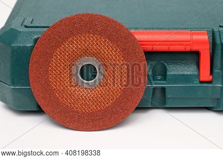 Abrasive Wheel, Grinding Wheel Orange On The Background Of The Green Toolbox. Abrasive Materials, Di