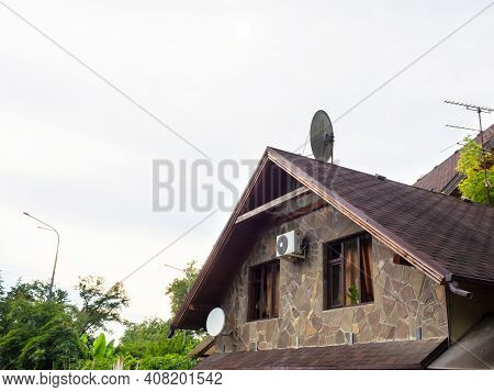 Top Of The House With Two Windows, Granite Cladding And A Tiled Roof With Antennas Against A Cloudy