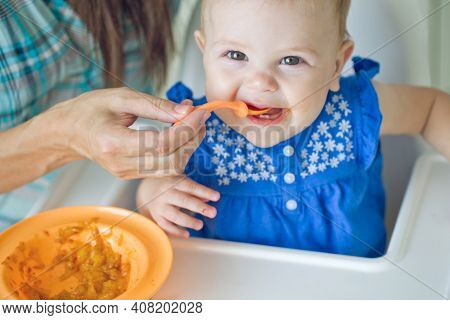 A Mother Feeds Her Baby With A Spoon. Mother Giving Healthy Food For Her Adorable Baby At Home. High