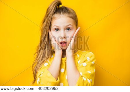 Closeup Portrait Of Excited Child Girl Touching Her Cheeks On Yellow Background