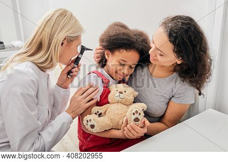 Hearing Exam. Child With Her Mother During A Hearing Test, Audiologist With Otoscope Checking Ear Of