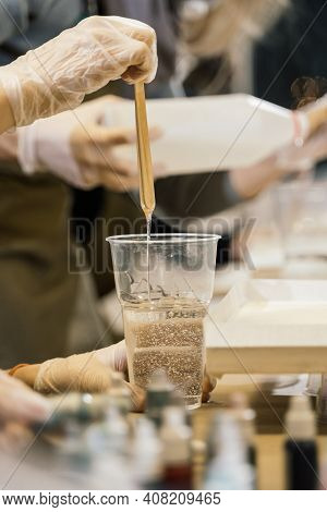 A Wooden Stick Is Lowered Into A Glass With Transparent Resin And The Resin Flows Down In A Thin Str