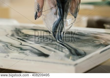 At The Workshop On Creating Fluid Art From A Plastic Cup, Black And White Resin Is Poured Onto The R