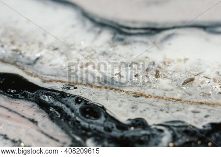 Beautiful Contemporary Art In Resin Art Technique. Seething Black Resin Flows Into Streams Of Milk A