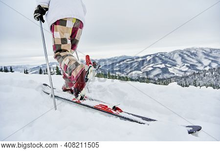 Close Up Of Alpine Skier In Winter Ski Pants Climbing The Snowy Hill With Beautiful Mountains On Bac