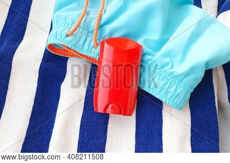 Mockup Of Red Glossy Deodorant Stick, Blank Roll For Deodorant, Striped Towel And Swim Shorts.