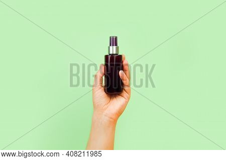Male Hand Holds Unbranded Brown Plastic Spray Bottle On Pastel Green Background. Cosmetic Bottle Con