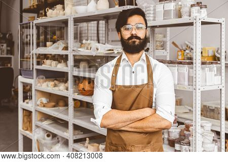 Portrait Of A Young Attractive Businessman Craftsman With A Beard And Mustache In His Workshop.. Pos