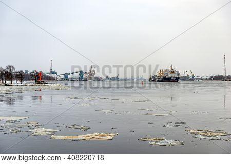 Riga, Latvia - February 9, 2021: Multiple Tugboats Work In Tandem To Assist Cargo Ship To Maneuver O