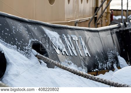 Riga, Latvia - February 9, 2021: Icy Hull With Mooring Hole And Ropes Tied To The Pier, Close-up