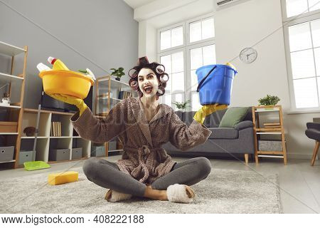 Funny Energetic Young Housewife Sitting On Floor And Holding Plastic Pail And Tub