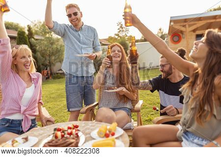 Group Of Young Friends Having Fun At Backyard Barbecue Party, Making A Toast, Drinking Beer, Eating