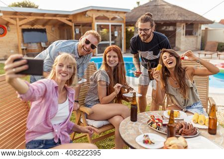 Group Of Friends Having A Backyard Poolside Barbecue Party, Having Fun Taking Selfies While Gathered