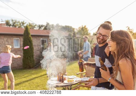 Group Of Friends Having A Backyard Barbecue Party, Grilling Meat, Drinking Beer, Playing Toss And Ca