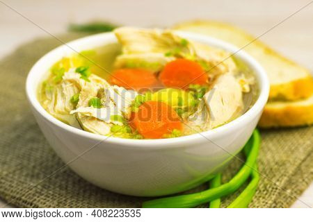 Chicken Soup Stew Broth And Vegetables In White Bowl On Old Rustic Wooden Cutting Board