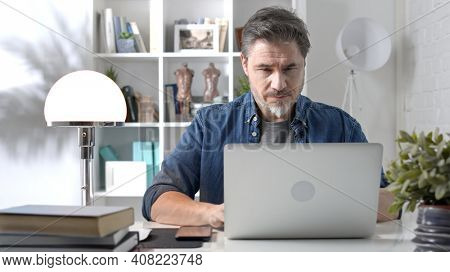 50s businessman with gray hair working from home. Man in casual sitting at desk using laptop computer, business manager online in home office.