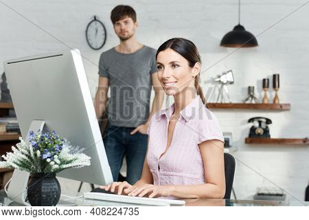 Attractive young woman sitting at desk, working with computer, typing on keyboard.