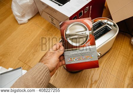 Paris, France - Feb 1, 2021: Overhead View Of Male Hand Holding Warranty Register Your Product Card
