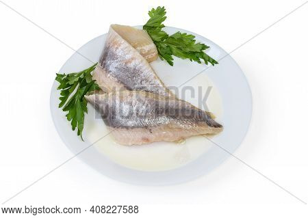 Two Pickled Mild Salted Fillets Of Atlantic Herring Without Skin On A White Dish With Twigs Of Fresh