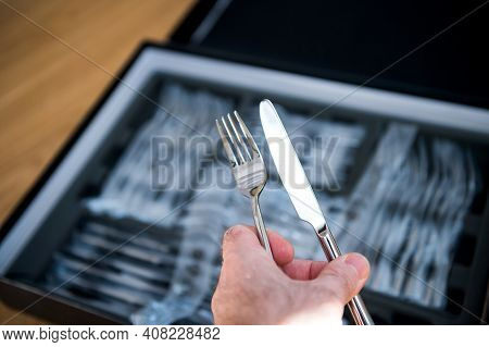 Pov Male Hand Holding New Cutlery Sets Flatware With Fork And Knife Being Unboxed From The Plastic P