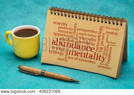 abundance mentality word cloud in a spiral notebook with a cup of coffee, positive mindset and win-win concept