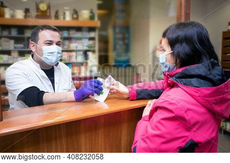 Pharmacy during Covid-19. Shopper in drugstore. People in protective medical masks buys medicine. Pharmacy, pharmacist. Covid and retail