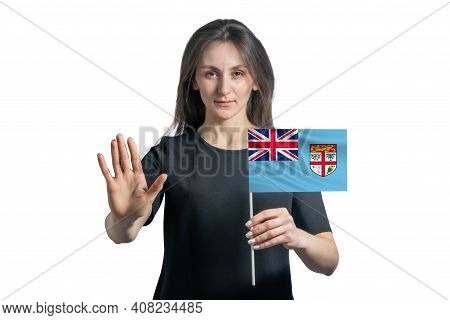 Happy Young White Woman Holding Flag Of Fiji And With A Serious Face Shows A Hand Stop Sign Isolated