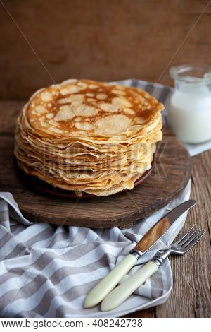 Thin Fried Pancakes On A Plate. Traditional Food For Shrovetide. Pancake With Sour Cream On A Wooden