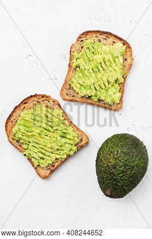 Whole Grain Toast With Mashed Avocado Isolated On Concrete Background, Top View, Copy Space