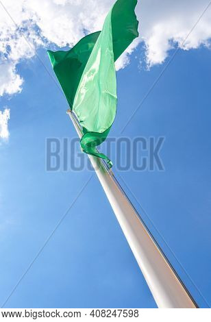 Green Flag Waving On The Blue Sky Background