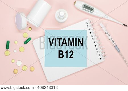 Notebook Page With Text Vitamin B12 On A Table With Pills And Syringe. Medical Concept.