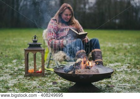 Young Blond Woman In A Wool Sweater Reads A Book Outside On The Grass By The Campfire. Burning Fire